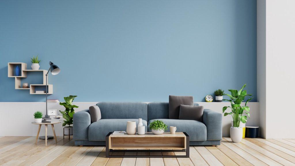 Das gemütliche Wohnzimmer in einem satten Blauton lädt zum Entspannen ein.